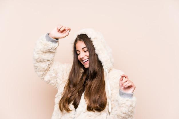 Młoda caucasian kobieta pozuje świętować specjalny dzień, skacze i podnosi ręki z energią.