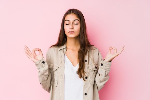 Młoda caucasian kobieta pozuje w różowej ścianie relaksuje po ciężkiego pracującego dnia, wykonuje joga.