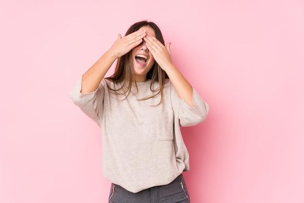 Młoda caucasian kobieta pozuje zakrywa oczy rękami, uśmiecha się szeroko czekający na niespodziankę.