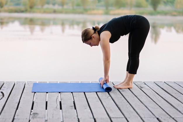 Młoda caucasian kobieta przekręca matę do jogi na zewnątrz w pobliżu rzeki na drewnianym molo rano