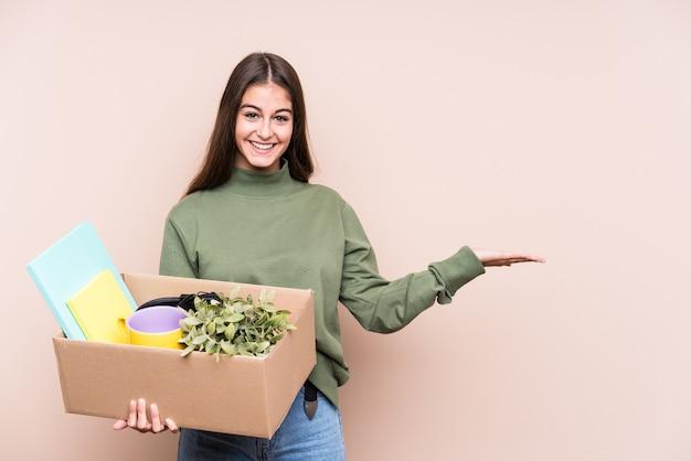 Młoda caucasian kobieta przenosi się do nowego domu odizolowywającego pokazywać odbitkową przestrzeń na dłoni i trzymać inną rękę na talii.