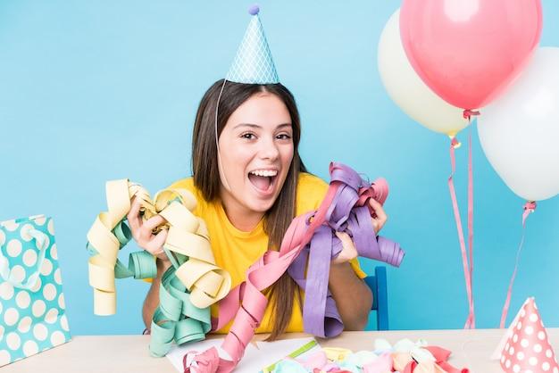 Młoda caucasian kobieta przygotowywa przyjęcia urodzinowego