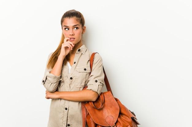 Młoda caucasian kobieta przygotowywająca dla podróży zrelaksowanego główkowania o coś patrzeje a.