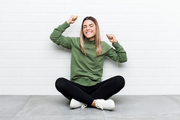 Młoda caucasian kobieta siedzi na podłodze świętuje wyjątkowy dzień, skacze i energicznie podnosi ręce.