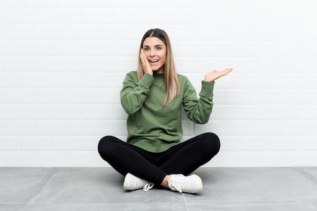 Młoda caucasian kobieta siedzi na podłodze trzyma kopii przestrzeń na dłoni, trzymać rękę nad policzkiem. zaskoczony i zachwycony.