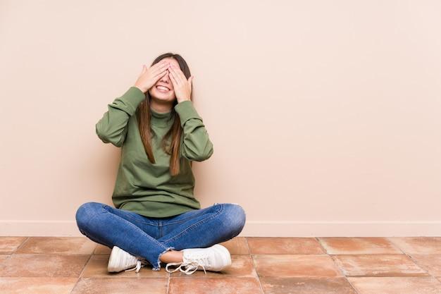 Młoda caucasian kobieta siedzi na podłoga odizolowywającej zakrywa oczy rękami, uśmiecha się szeroko czekający na niespodziankę.