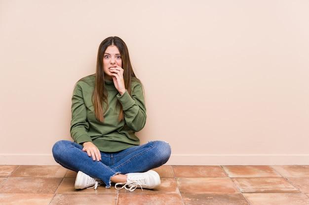 Młoda caucasian kobieta siedzi na podłoga odizolowywał gryzących paznokcie, nerwowych i bardzo niespokojnych.