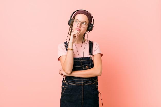 Młoda caucasian kobieta słucha muzyka patrzeje z ukosa z wątpliwym i sceptycznym wyrażeniem