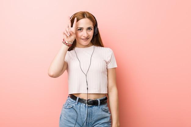 Młoda caucasian kobieta słucha muzyka pokazuje zwycięstwo znaka i uśmiecha się szeroko.
