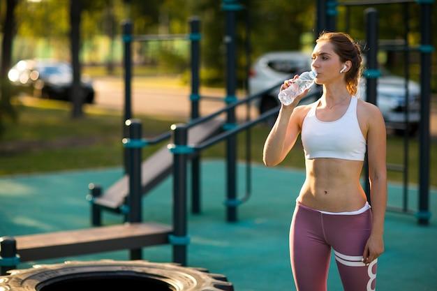 Młoda caucasian kobieta trenuje na plenerowym boisku i pije wodę z butelki. fitness trening siłownia na świeżym powietrzu