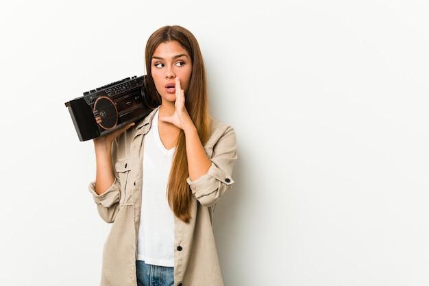 Młoda caucasian kobieta trzyma blaster guetto mówi sekretną gorącą hamującą wiadomość i patrzeje na boku