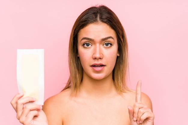 Młoda caucasian kobieta trzyma depilacyjnego zespół odizolowywał pokazywać liczbę jeden z palcem.