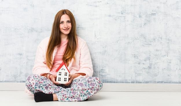 Młoda caucasian kobieta trzyma domową ikonę szczęśliwą, uśmiechniętą i rozochoconą.