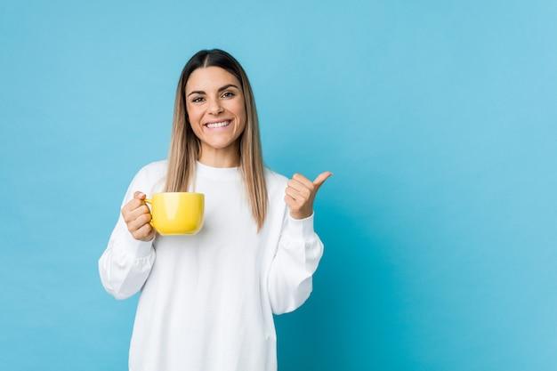 Młoda caucasian kobieta trzyma filiżankę uśmiecha się kciuk up i podnosi