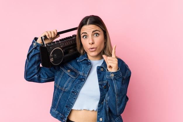 Młoda caucasian kobieta trzyma guetto blaster ma niektóre doskonałego pomysł, pojęcie twórczość.