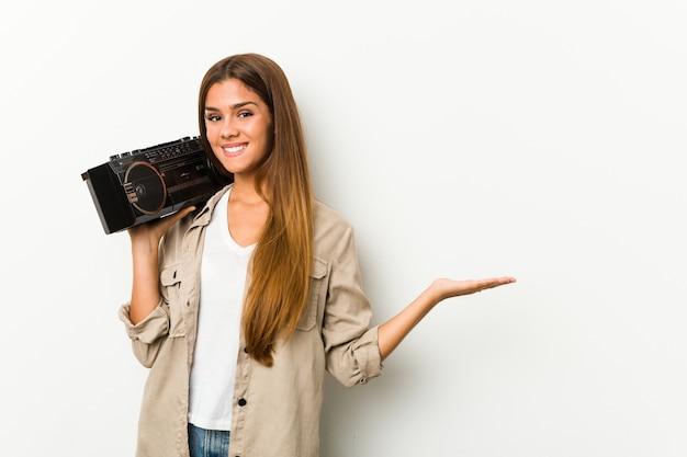Młoda caucasian kobieta trzyma guetto blaster pokazuje odbitkową przestrzeń na dłoni i trzyma inną rękę na talii.