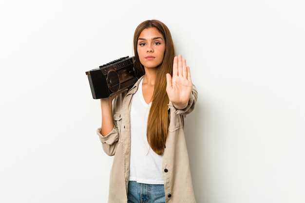 Młoda caucasian kobieta trzyma guetto blaster pozycję z szeroko rozpościerać ręka seansu przerwy znakiem, zapobiega ciebie.