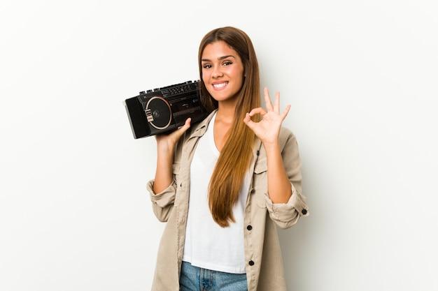 Młoda caucasian kobieta trzyma guetto blaster rozochoconego i ufnego pokazuje ok gest.