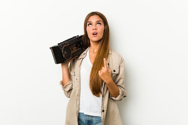 Młoda caucasian kobieta trzyma guetto blaster wskazuje do góry z rozpieczętowanym usta.