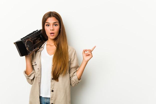 Młoda caucasian kobieta trzyma guetto blaster wskazuje strona