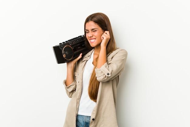 Młoda caucasian kobieta trzyma guetto blaster zakrywa ucho z rękami.