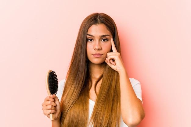 Młoda caucasian kobieta trzyma hairbrush wskazuje jego świątynię z palcem, myśleć, skupiający się na zadaniu.