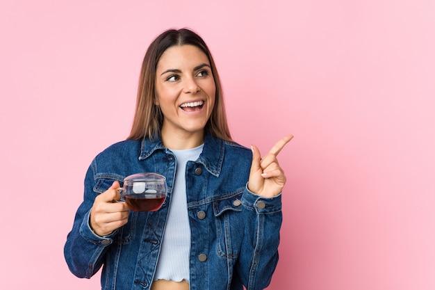 Młoda caucasian kobieta trzyma herbacianą filiżankę ono uśmiecha się radośnie wskazujący z palcem wskazującym daleko od.