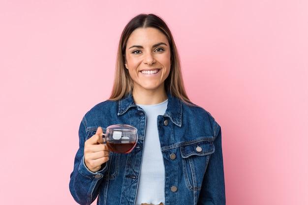 Młoda caucasian kobieta trzyma herbacianą filiżankę szczęśliwa, uśmiechnięta i rozochocona.