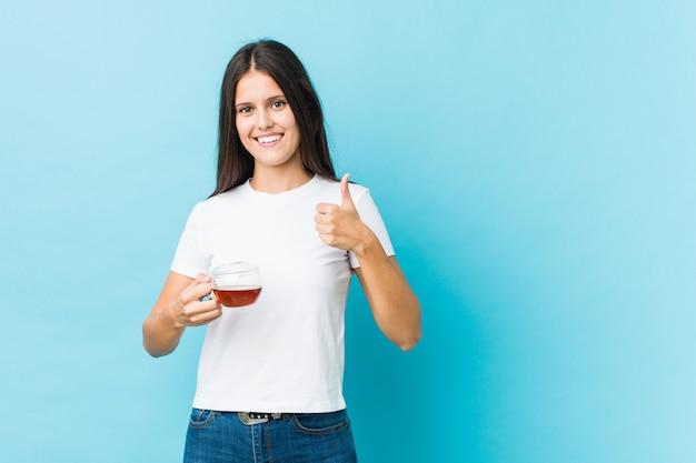 Młoda caucasian kobieta trzyma herbacianą filiżankę uśmiecha się kciuk up i podnosi