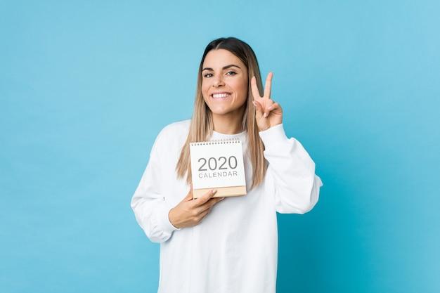 Młoda caucasian kobieta trzyma kalendarz 2020 pokazuje znak zwycięstwa i uśmiecha się szeroko.