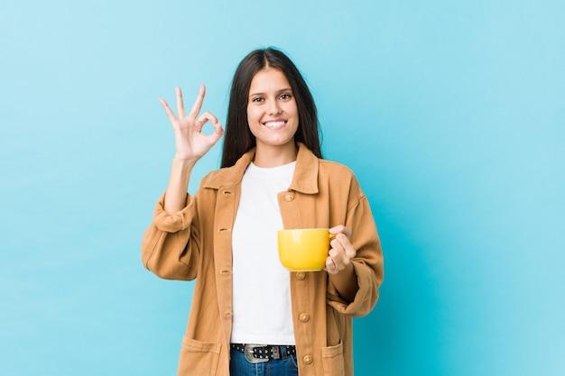 Młoda caucasian kobieta trzyma kawowego kubek rozochoconego i ufnego pokazuje ok gest.