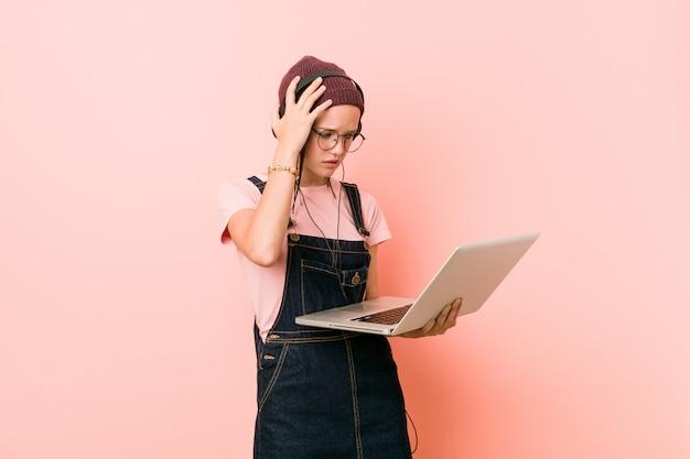 Młoda caucasian kobieta trzyma laptop jest zszokowana, przypomniała sobie ważne spotkanie.