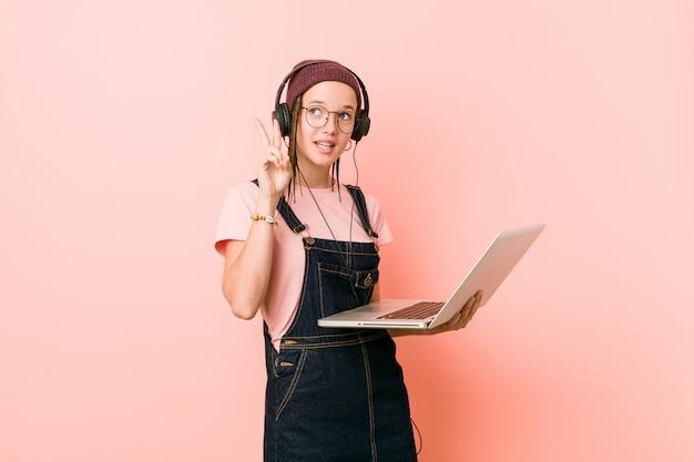 Młoda caucasian kobieta trzyma laptop pokazuje zwycięstwo znaka i ono uśmiecha się szeroko.