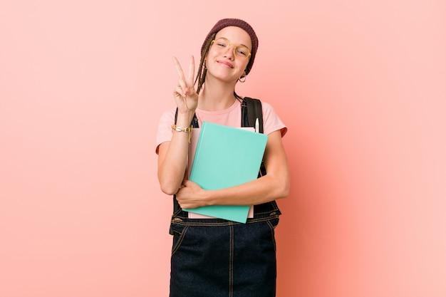 Młoda caucasian kobieta trzyma niektóre notatniki pokazuje numer dwa z palcami.