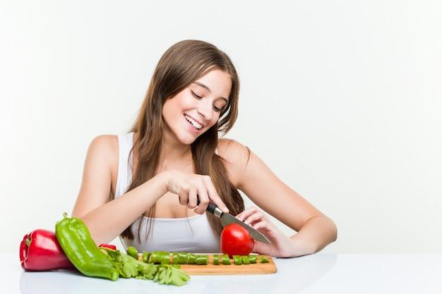 Młoda caucasian kobieta trzyma nóż i ciie warzywa
