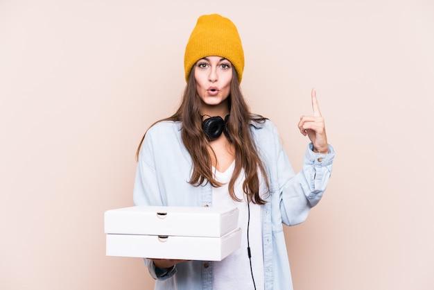 Młoda caucasian kobieta trzyma pizze ma niektóre doskonałego pomysł