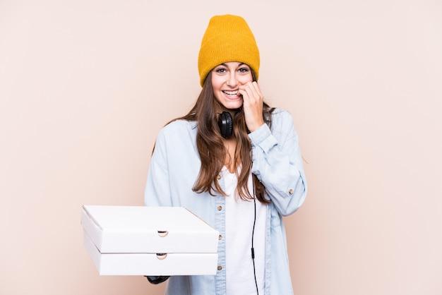 Młoda caucasian kobieta trzyma pizze obgryzające paznokcie, nerwowa i bardzo niespokojna.