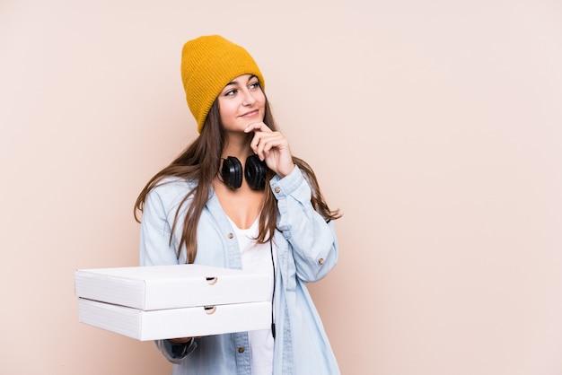 Młoda caucasian kobieta trzyma pizze patrzeje z ukosa z wątpliwym i sceptycznym wyrażeniem.