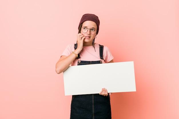 Młoda caucasian kobieta trzyma plakat obgryzającymi paznokcie, nerwowa i bardzo niespokojna.