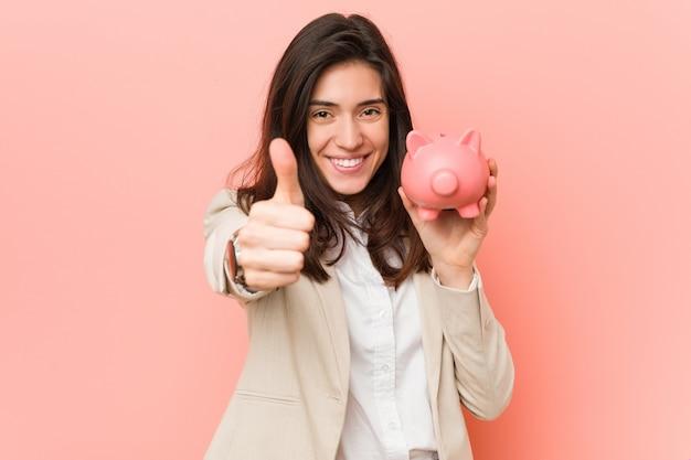 Młoda caucasian kobieta trzyma prosiątko banka