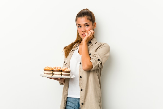 Młoda caucasian kobieta trzyma słodkich ciastka gryźć paznokcie, nerwowa i bardzo niespokojna.