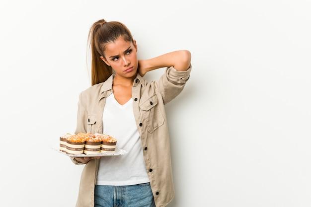 Młoda caucasian kobieta trzyma słodkich torty dotyka plecy głowa, myśleć i robi wyborowi.