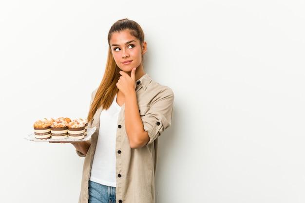 Młoda caucasian kobieta trzyma słodkich torty patrzeje z ukosa z wątpliwym i sceptycznym wyrażeniem.