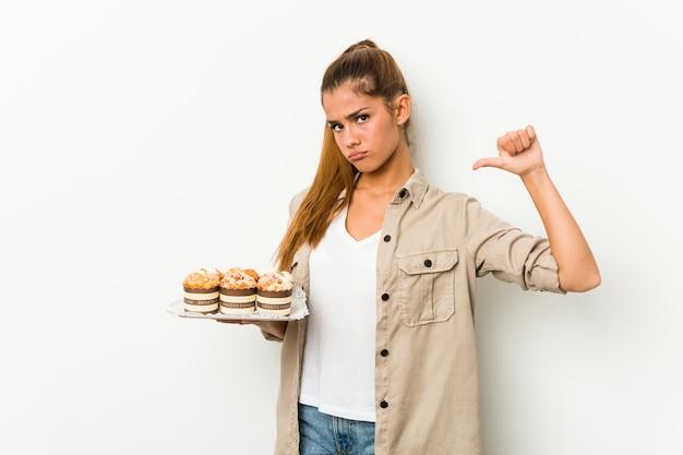 Młoda caucasian kobieta trzyma słodkie ciasta czuje się dumna i pewna siebie, przykład do naśladowania.