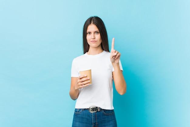 Młoda caucasian kobieta trzyma takeaway kawę pokazuje liczbę jeden z palcem.