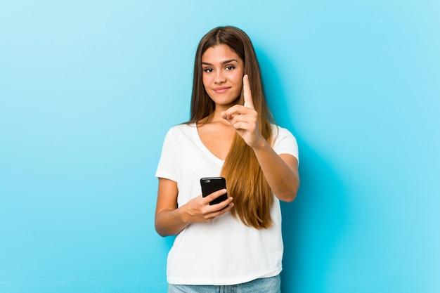 Młoda caucasian kobieta trzyma telefon pokazuje liczbę jeden z palcem.