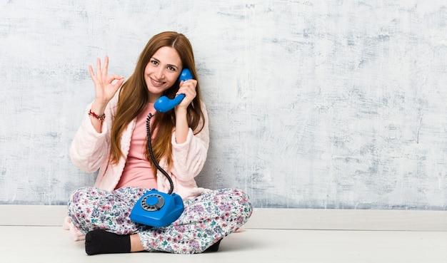 Młoda caucasian kobieta trzyma telefon stacjonarnego rozochoconego i ufnego pokazuje ok gest.