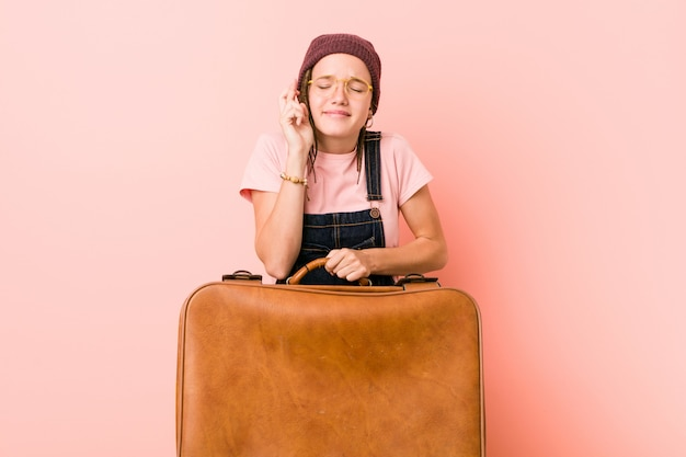 Młoda caucasian kobieta trzyma walizkę krzyżuje palce dla mieć szczęście