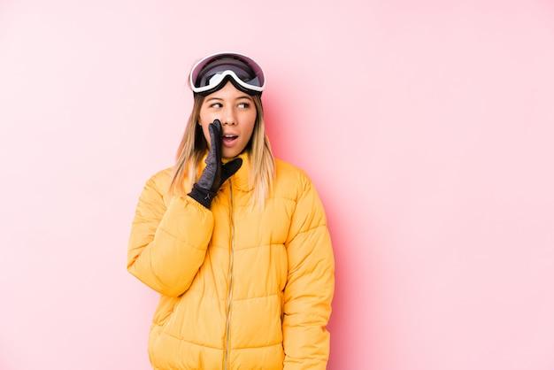 Młoda caucasian kobieta ubrana w narty w różowej ścianie mówi sekretną wiadomość o hamowaniu na gorąco i patrzy na bok
