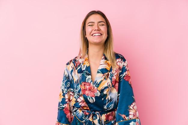 Młoda caucasian kobieta ubrana w piżamę śmieje się i zamyka oczy, czuje się zrelaksowana i szczęśliwa.